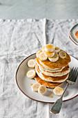 Stack of banana pancakes with fresh banana slices