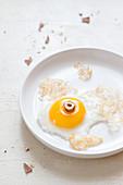 A fried egg with half a hazelnut