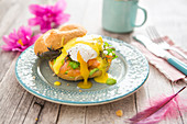 Eggs Benedict with salmon, avocado cream and hollandaise sauce