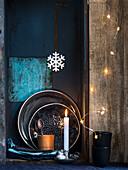 Brennende Kerze neben Lichterkette