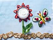Kreative Blume und Schmetterling aus Obst und Gemüse mit Beerenblütenblättern, Joghurt und Selleriestiel