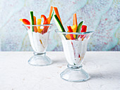 Sliced zucchini, red, green and yellow bell pepper and carrot in glass cups filled with creamy ranch dressing