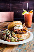 A cheeseburger with bacon and a bloody mary drink