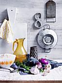 Stillleben mit Zwiebeln, Knoblauch, Rosmarin und Küchenutensilien