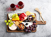 Selection of cheese and appetizers, red wine, camembert, brie, cheddar, cracker, grapes, nuts and honey