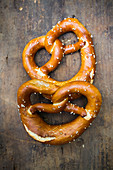 Two pretzels on a wooden background (top view)