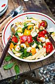 Nudelsalat mit Tomaten, Mozzarella und Babyspinat auf Tisch im Freien