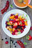 Fruit salad with summer fruits on a wooden table