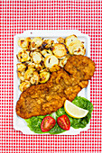 Breaded schnitzel with fried potatoes on a red and white checkered tablecloth