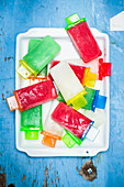 Various homemade popsicles on a blue wooden background