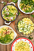 Various potato salads in bowls on a wooden background (top view)