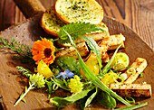 Wild herb salad with roasted tofu, yellow tomatoes and a herb baguette