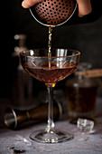 Ein Manhattan-Cocktail wird in ein Glas gegossen