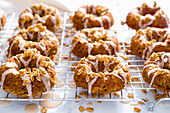 Apple muesli donuts with icing and granola on a cooling grid