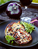 Oven-baked aubergines with olives, almonds and cheese