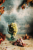Still life with grapes and autumn leaves