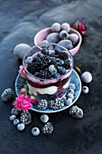 A layered dessert with fresh yoghurt, berry mash, frozen blueberries and blackberries