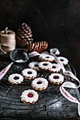 Linzer wreath biscuits on a cooling grid with a Christmas ribbon