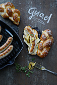 Beer sausages in plaited lye bread rolls