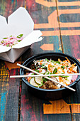 Asian fried chicken rice bowl with pickled carrot, sauce, and sesame seeds in to-go container