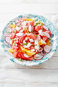 Watermelon salad with orange, radish and red onion