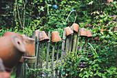 Tontöpfe auf dem Gartenzaun