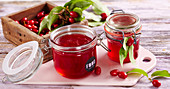 Homemade cornelian cherry jelly in glass jars on a wooden board