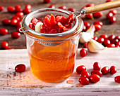 Homemade cornelian cherry vinegar with garlic and fruit vinegar in a mason jar with a strainer