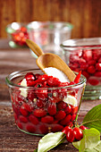 Sweet and sour pickled cornelian cherries in a glass bowl on a wooden background