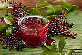 Homemade strawberry and elderberry jam in a glass on a green wooden surface
