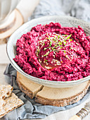 Roasted beetroot white bean hummus decorated with sprouts (vegan)