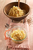 Sauerkraut made from pointed cabbage in a wooden bowl and a jar