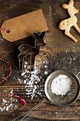 Backstilleben mit Rehkitz-Ausstecherle, Puderzucker im Sieb und Geschenkanhänger