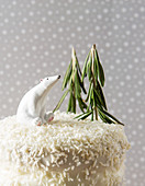 Coconut cake decorated for Christmas with rosemary trees and a polar bear, in a snowy setting