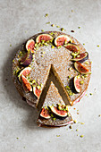 Victoria sponge cake deorated with figs, pistachio nuts and icing sugar