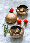 Raw portobello mushrooms, thyme sprigs and cherry tomatoes