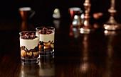 Frozen Tiramisu serviert in Gläsern vor dunklem Hintergrund
