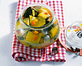 Pickled courgettes with turmeric and mustard seeds in a jar