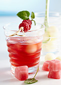 Non-alcoholic punch with raspberries and honey dew melon served with pink ice cubes