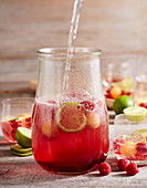 Raspberry and melon punch with champagne and limes in a jar