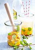 Orange and lime punch with cachaca and mint in jars