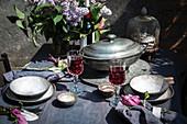 Gedeckter Tisch mit Rotwein und Flieder