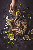 Fresh Tiger Prawns and lemon slices placed on a dark tabletop with one hand taking a tiger prawn