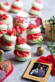 Macarons mit roter Cremefüllung garniert mit Cremetupfen