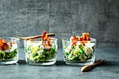 Caesar salad with fried bacon in glasses
