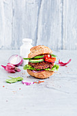 A veggie burger with cucumber and tomatoes
