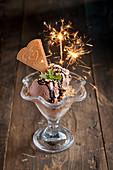 Schokoladeneisbecher mit gehackten Nüssen und Wunderkerzen