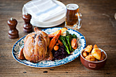 A whole roast chicken with vegetables