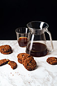A pile of chocolate cookies with pour over coffee
