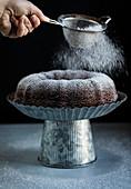 Napfkuchen mit Puderzucker bestreuen
